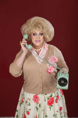 Drag queen holding telephone over maroon background