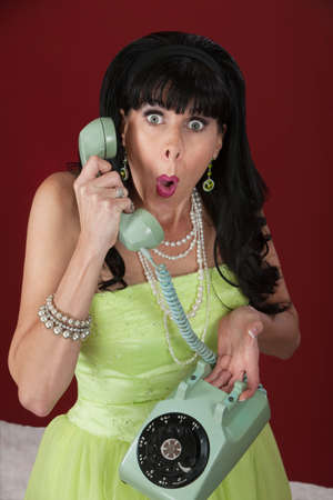 Surprised looking retro-styled woman holding a rotary telephone photo