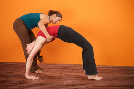 yoga pants: Yoga instructor helps student perfrom Urdhva Dhanurasana over orange background Stock Photo
