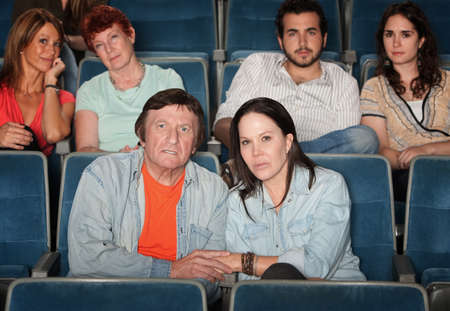 mesmerized: Group of upset audience watch movie in theater
