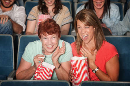 Two laughing women with popcorn bags at a picture show