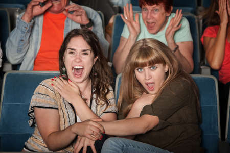 Scared friends in theater holding hands and screaming photo
