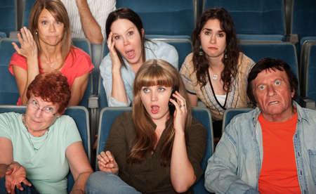 molesto: Una mujer fuerte en el teléfono molesta público en el teatro