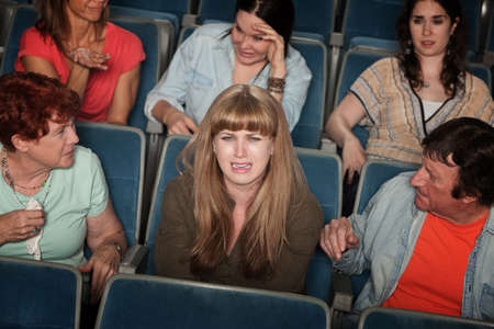 embarrassing: Weeping woman and distracted people in the audience