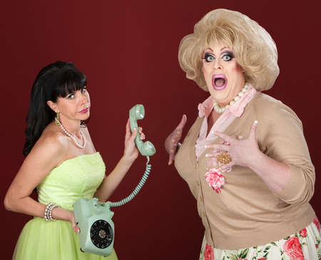 Retro-styled woman holding telephone with scared drag queen