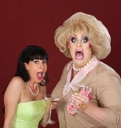 Screaming woman and drag queen with martinis over maroon background photo
