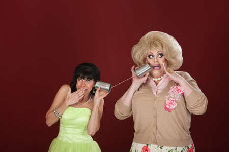tin can telephone: Retro-styled woman talks to drag queen on tin can phone