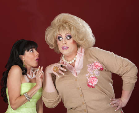 Woman and drag queen holding cigarettes gossiping photo