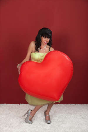 Smiling woman holds huge red heart shaped balloon photo