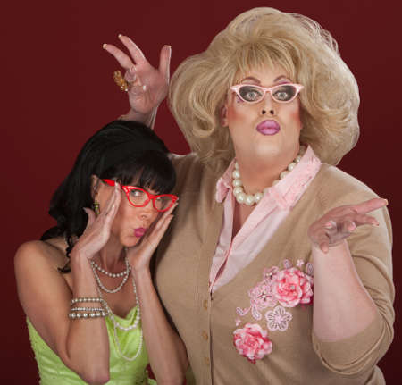 puckered lips: Woman and drag queen with thick eyeglasses make faces