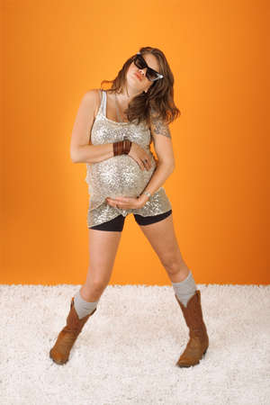 Dancing pregnant woman with hand on tummy over orange background