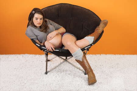 beautiful womb: Pretty Caucasian woman relaxing on chair over orange background