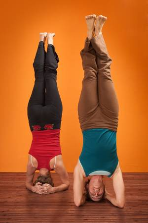 headstand: Two women perform Sirsasana headstand positions over orange background