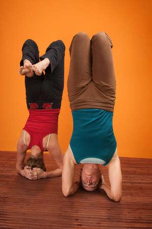 Two women perfrom Vrisikasana yoga posture over orange background Stock Photo