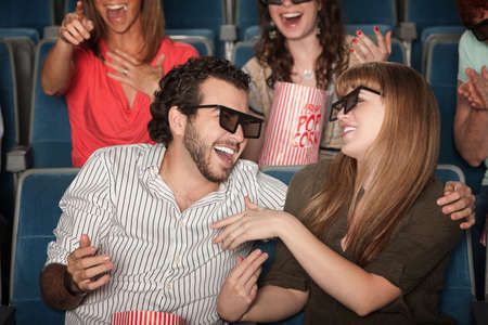 Couple with 3D glasses in theater laughing together photo