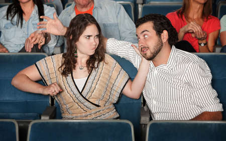 Irked woman gestures to punch man in theater photo
