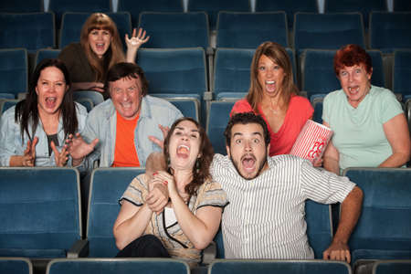 Group of seven scared people screaming in a theater photo