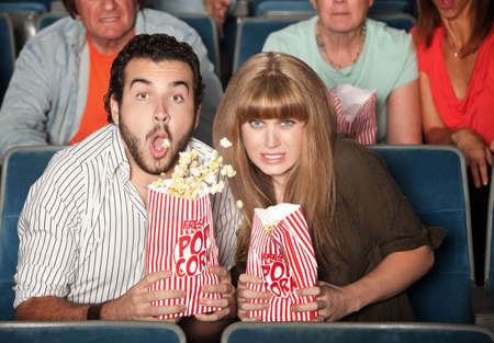 Scared Caucasian couple in theater spill their popcorn photo