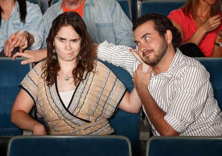 Girlfriend annoyed with rude man in theater  版權商用圖片