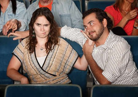 pervert: Girlfriend annoyed with rude man in theater  Stock Photo