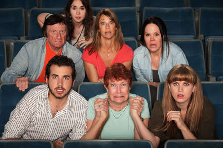 Group of scared people watching movie in a theater photo