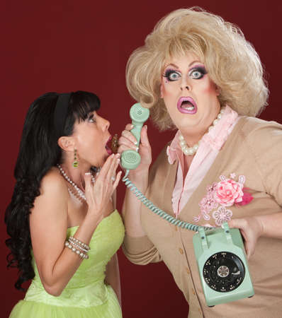 Surprised man in drag with friend and telephone photo