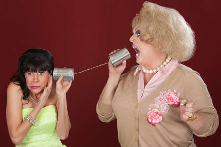 tin can phone: Woman with friend in drag talk through tin cans Stock Photo