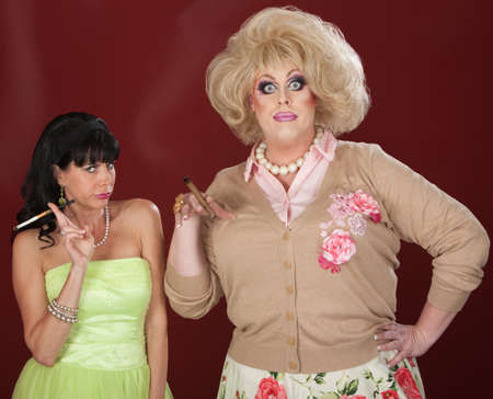Curious drag queen and friend with cigarettes over maroon background photo