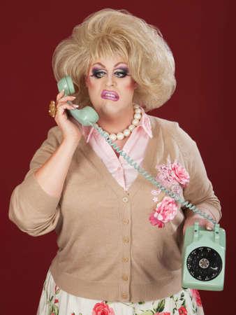 Sneering retro style drag queen on telephone photo