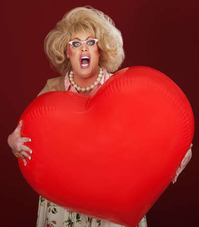 Screaming drag queen with huge red heart shaped balloon