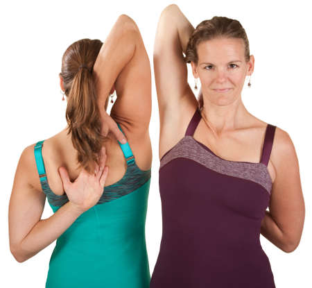 hands behind back: Two fit women stretch their shoulders over white background