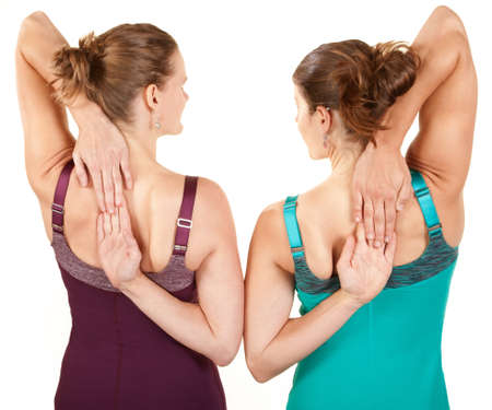 Two fit women stretching their arms over white background photo