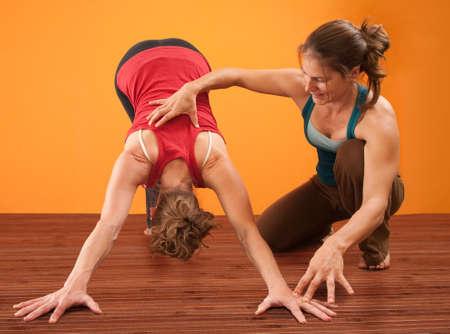 educadores: Profesor de yoga ayuda a los estudiantes realizar Adho Mukha postura de yoga Svanasana