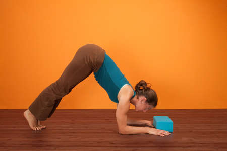 wood block: Fit woman practicing yoga with foam stability block