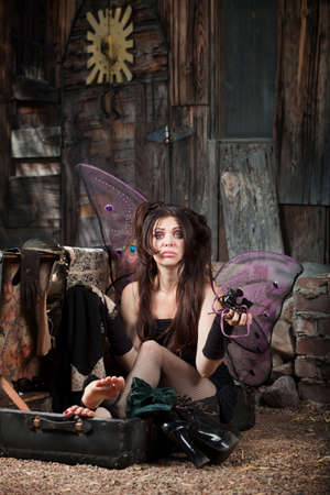 Sad Faery sitting in suitcase holding Jeweler glasses photo