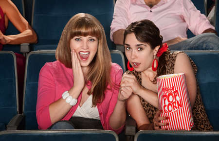 clasped: Two amazed ladies with bag of popcorn in theater Stock Photo