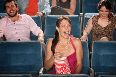 Laughing woman with popcorn in a theater photo