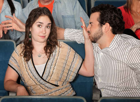 misbehaving: Irritated girlfriend stops misbehaving boyfriend in theater Stock Photo