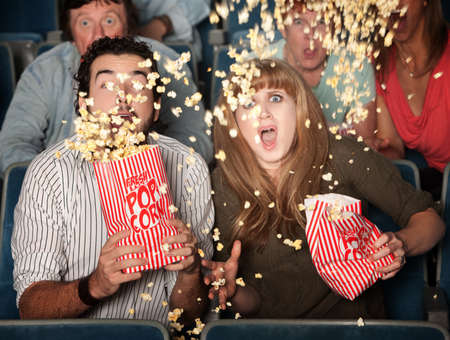 suspense: Scared couple jump in their seats with spilled popcorn Stock Photo