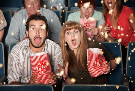 Group of frightened people watching movie spill popcorn photo