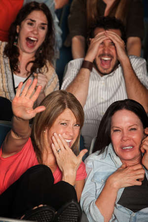 grandstand: Screaming people curled up in seats at a movie theater Stock Photo