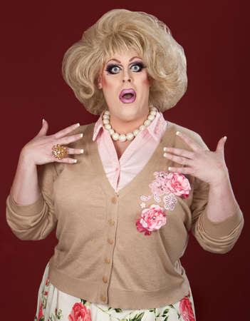 drag queen: Worried male drag queen over maroon background