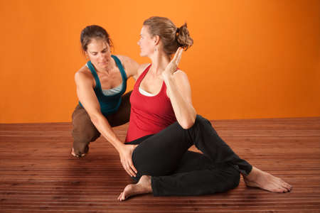 instructeur: Coach en leerling in de yoga sportkleding