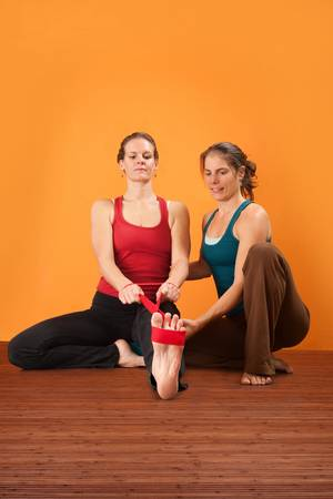 straps: Yogasana instructor helps student stretch her leg Stock Photo