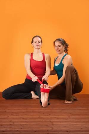 yoga pants: Yogasana instructor helps student stretch her leg Stock Photo