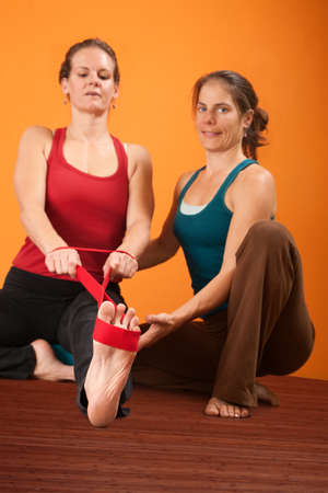 hamstring: Yoga trainer helps student stretch with elastic band Stock Photo