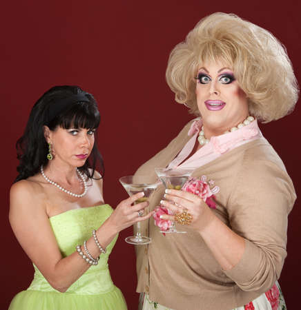 Happy drag queen with suspicious woman toast martinis photo