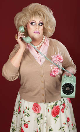 Confused drag queen on phone call over maroon background 스톡 콘텐츠