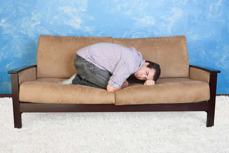 stubborn: Upset young Caucasian man in fetal position on sofa