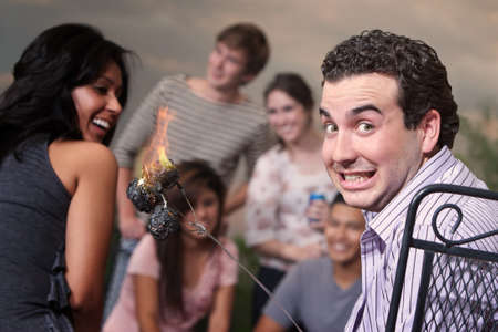 Embarrassed man with burning marshmallows at a cookout photo
